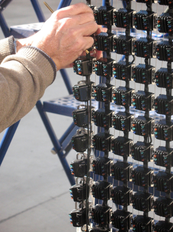NOVO engineer installing a 16-module segment on a flexible mesh outdoor video display